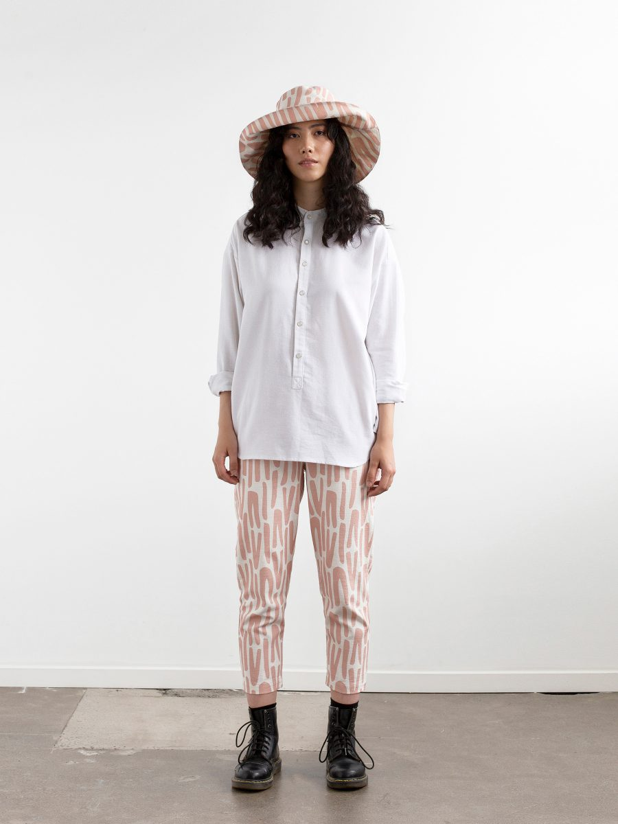 Full length photograph of model against a white wall wearing doc martins with calf length pants, white button front shirt and floppy wide brimmed hat. Hat and pants feature SURFACE 1°22 scattered stripes pattern in Rose and white.