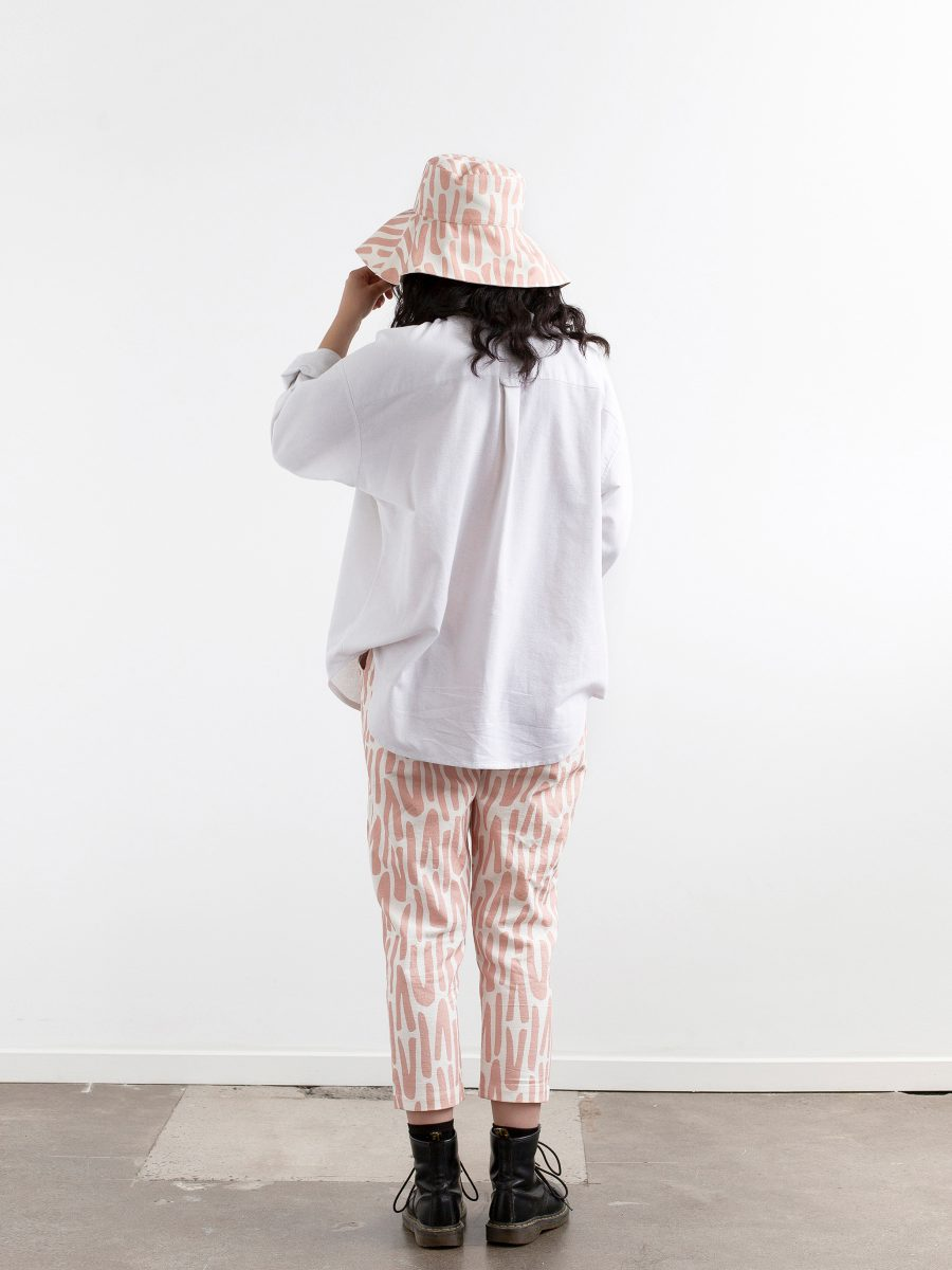 Back view - full length photograph of model against a white wall wearing doc martins with calf length pants, white button front shirt and floppy wide brimmed hat. Hat and pants feature SURFACE 1°22 scattered stripes pattern in Rose and white.