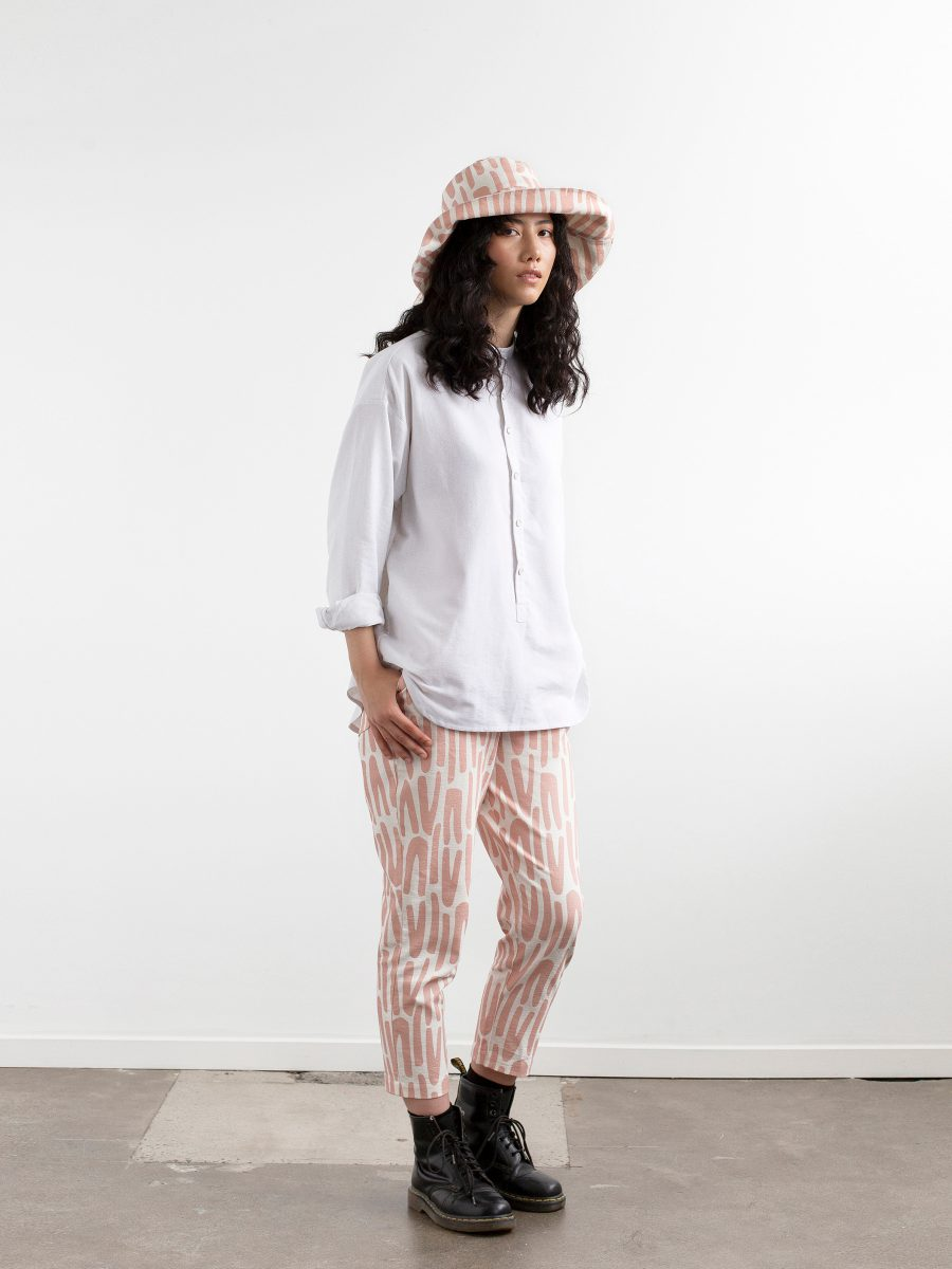 Side view - Full length photograph of model against a white wall wearing doc martins with calf length pants, white button front shirt and floppy wide brimmed hat. Hat and pants feature SURFACE 1°22 scattered stripes pattern in Rose and white.