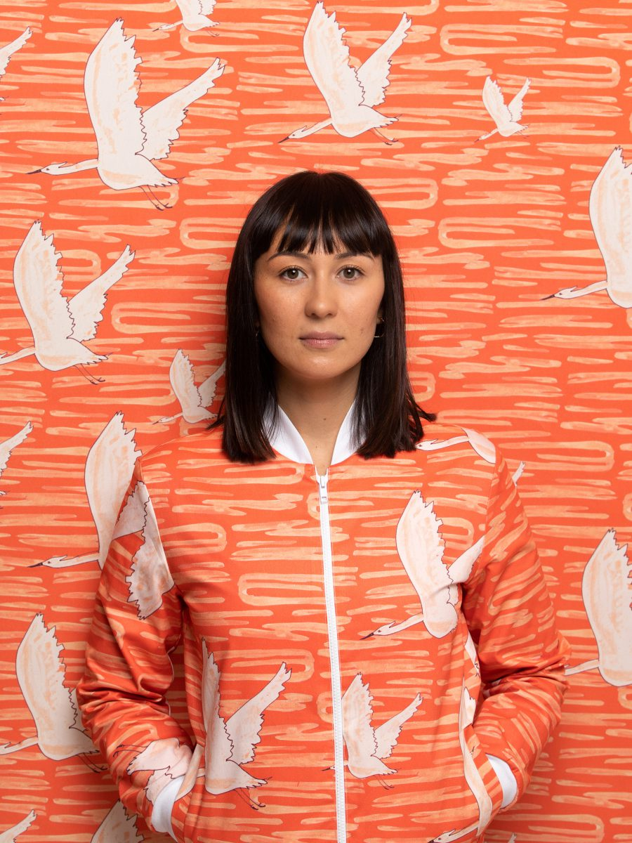 Girl wearing orange and white bird patterned bomber jacket with her hands in the pockets leaning against matching patterned background.