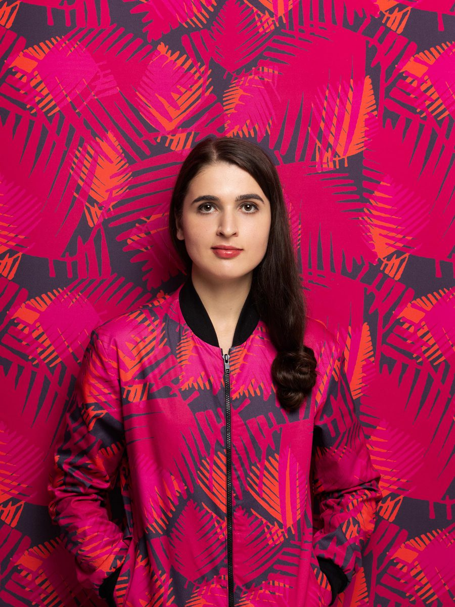 Girl wearing Magenta, Orange and Purple palm frond patterned bomber jacket with her hands in the pockets leaning against matching patterned background.