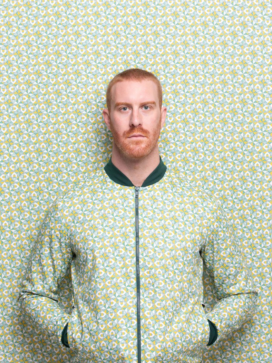 Fair, tall man wearing green geometric patterned bomber jacket with his hands in the pockets leaning against matching patterned background.