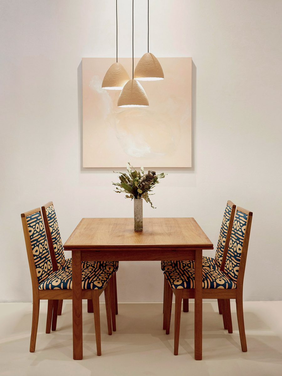 Interior design photo featuring a four seater wooden table with floral arrangement in the centre and four chairs featuring SURFACE 1°22 dot dot dash geometric pattern in teal, clay and lemon colours with abstract painting on the white wall and clay lights dropped from ceiling