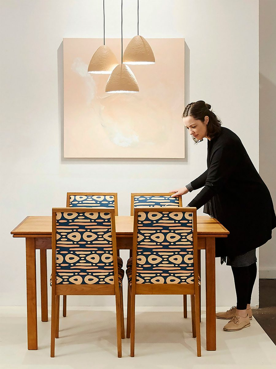 Woman standing at four seater wooden table pulling out one chair featuring SURFACE 1°22 dot dot dash geometric pattern in teal, clay and lemon colours with abstract painting on the white wall and clay lights dropped from ceiling