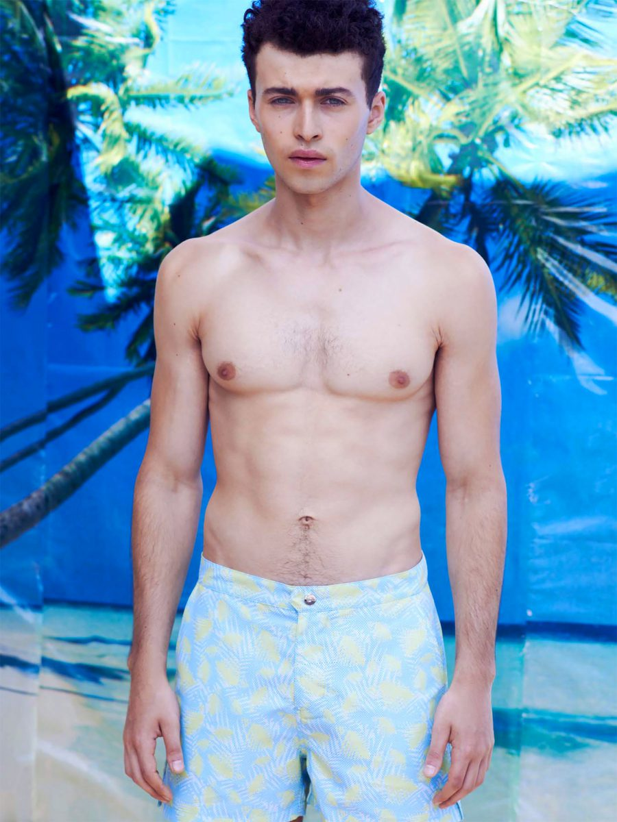 Shirtless man standing in front of palm trees and the ocean wearing board short swim trunks featuring light blue and yellow SURFACE 1°22 botanical leaf pattern 2016