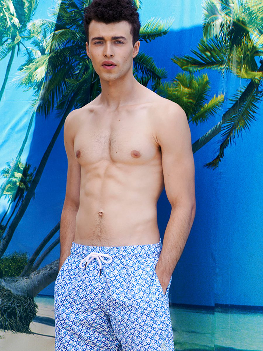 Shirtless man standing in front of palm trees and the ocean wearing board short swim trunks featuring blue and white SURFACE 1°22 geometric pattern 2016