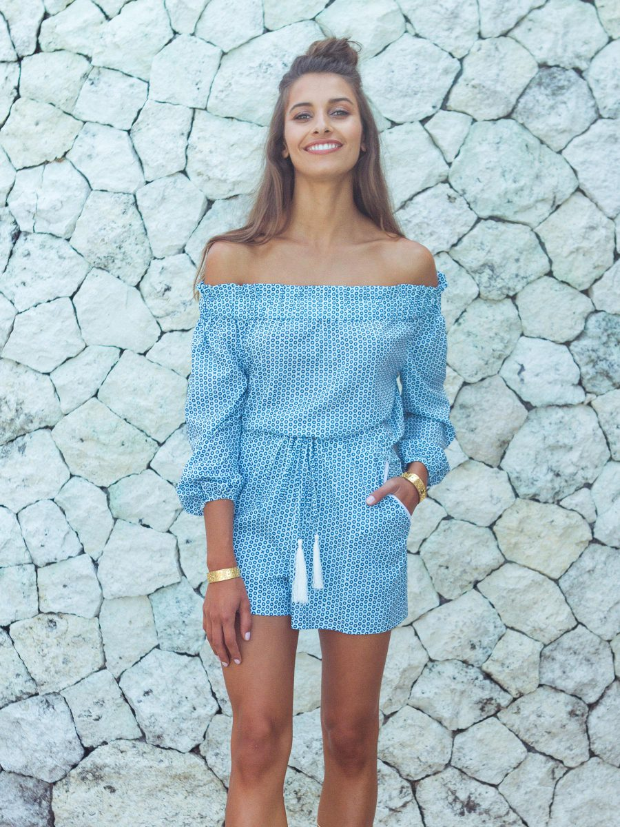 Three quarter length portrait photo of a female model wearing an above the knee and off the shoulder long sleeved playsuit featuring SURFACE 1°22 XO pattern, gold bangles and long beach hair against a stone wall.
