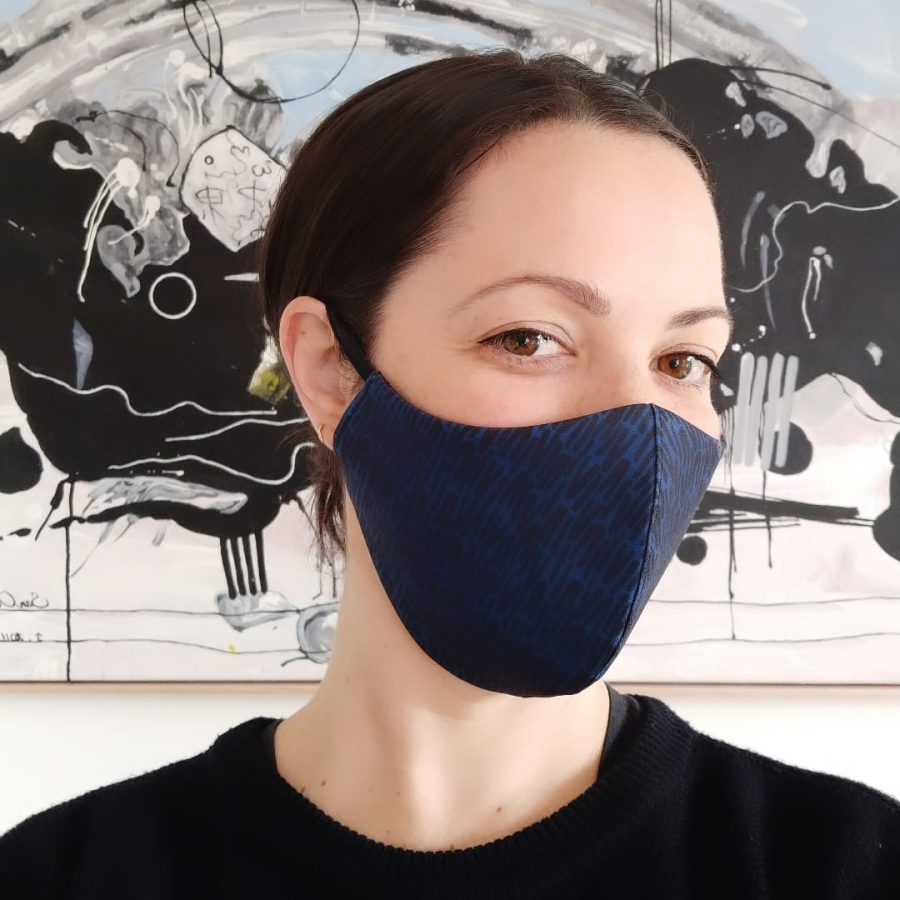 Photograph of SURFACE 1°22 founder and head designer - Emily Wills wearing face mask featuring her scattered stripes print design and an abstract artwork in the background.